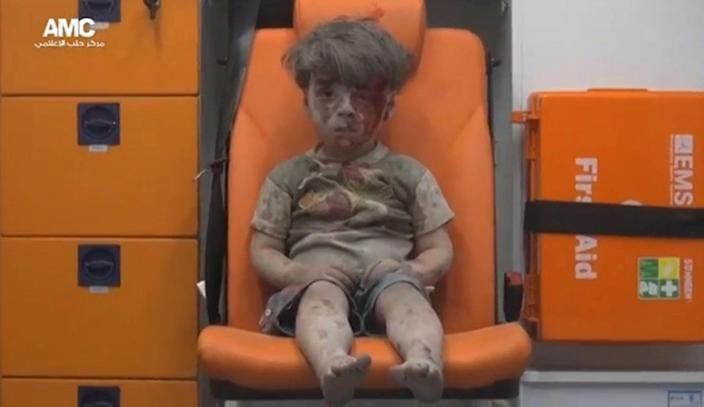 <p>AUG. 17, 2016 — A still image from a video posted on social media said to be shot in Aleppo, shows a boy with bloodied face sitting in an ambulance, after an airstrike, Syria. (Social Media via Reuters) </p>