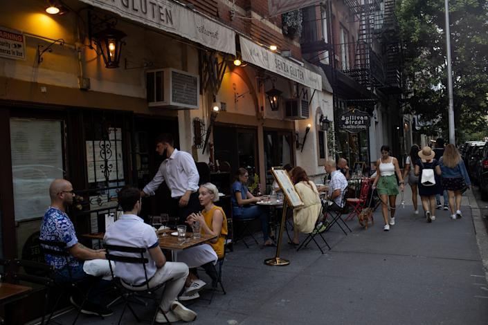 People seated at sidewalk tables outside a restaurant.