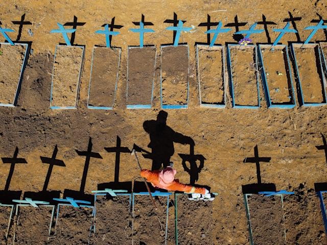 TOPSHOT - Aerial view showing a gravedigger standing at the Nossa Senhora Aparecida cemetery where COVID-19 victims are buried daily, in the neighbourhood of Taruma, in Manaus, Brazil, on June 2, 2020 during the novel coronavirus pandemic. - The pandemic has killed at least 375,555 people worldwide since it surfaced in China late last year, according to an AFP tally at 1100 GMT on Tuesday, based on official sources. Brazil is the fourth worst-hit country with 29,937 deaths so far. (Photo by Michael DANTAS / AFP) (Photo by MICHAEL DANTAS/AFP via Getty Images)