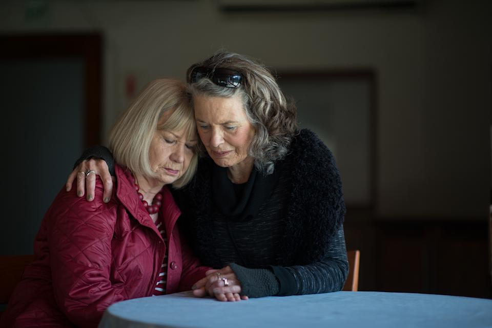 A senior lady supporting her friend after receiving sad bad news by holding hands comforting words and hugging her in support Stellenbosch Cape Town South Africa
