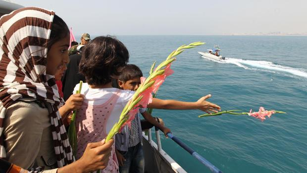 Iranian children throw flowers into the sea as they commemorate the 24th anniversary of the downing of Iran Air Flight 655 by the U.S. Navy, at the port of Bandar Abbas, Iran, July 2, 2012. / Credit: ATTA KENARE/AFP/Getty