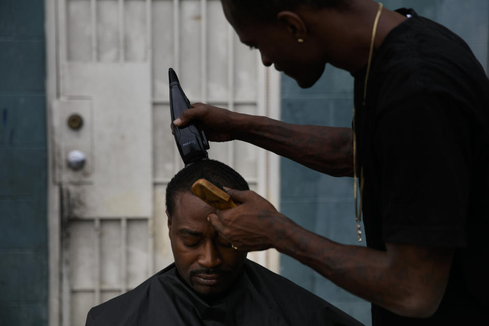 """Eric Frierson, 37, gets an haircut from Kenneth Cox, 32, outside an apartment building at the Imperial Courts housing project in the Watts neighborhood of Los Angeles, Wednesday, June 17, 2020. Frierson laments losing focus on becoming a good athlete and falling prey to the """"distractions,"""" such as the violence he witnessed or the signs of it. """"If you don't see it, you see the aftermath,"""" he said. """"You come outside and see the sidewalk stained with blood. It doesn't go anywhere. Every time you go by it, you see it."""" (AP Photo/Jae C. Hong)"""