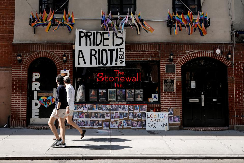 People wearing protective masks walk past the closed Stonewall Inn, after the U.S. Supreme Court delivered a watershed victory for LGBT rights, in New York City, U.S., June 15, 2020. REUTERS/Brendan McDermid