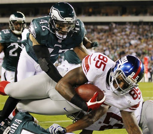 Philadelphia Eagles strong safety Kurt Coleman (42) tackles New York Giants tight end Martellus Bennett (85) during the first half of an NFL football game, Sunday, Sept. 30, 2012, in Philadelphia. (AP Photo/Mel Evans)