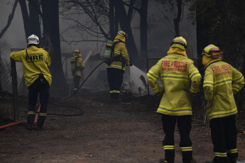 Fire and Rescue NSW fire fighters extinguish a structural firein Lake Tabourie on the Princes Highway between Bateman's Bay and Ulladulla in NSW in December. Source: AAP