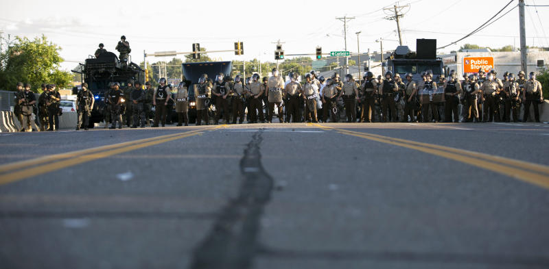 Police officers keep watch while demonstrators (not pictured) protest the death of black teenager Michael Brown in Ferguson, Missouri, Aug. 12, 2014. (Mario Anzuoni / Reuters)