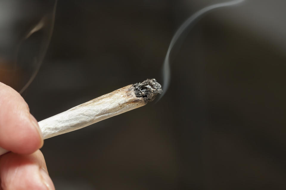 Close-up image of a hand holding a lit marijuana joint against dark gray background
