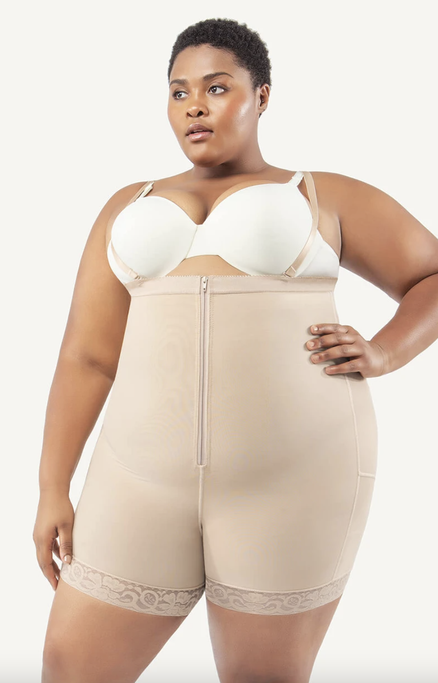 plus size model with short black hair wearing a white bra and beige body shaping shorts