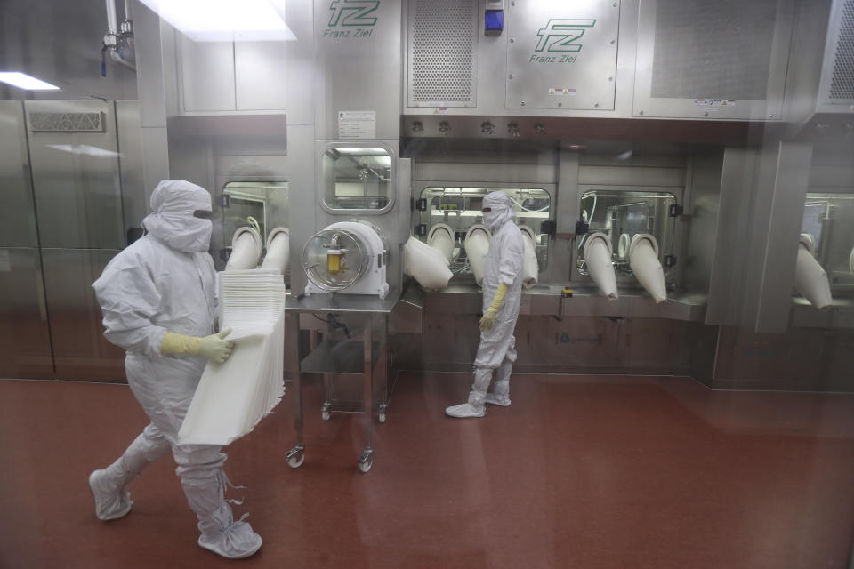 Employees operate a filling machine inside a laboratory at the Serum Institute of India, in Pune, India, Thursday, Jan. 21, 2021. The world's largest vaccine maker, based in India, will be able to restart exports of AstraZeneca doses by June if new coronavirus infections subside in the country, its chief executive said Tuesday, April 6. But a continued surge could result in more delays because the Serum Institute of India would have to meet domestic needs, Adar Poonawalla warned in an interview with The Associated Press. (AP Photo/Rafiq Maqbool)
