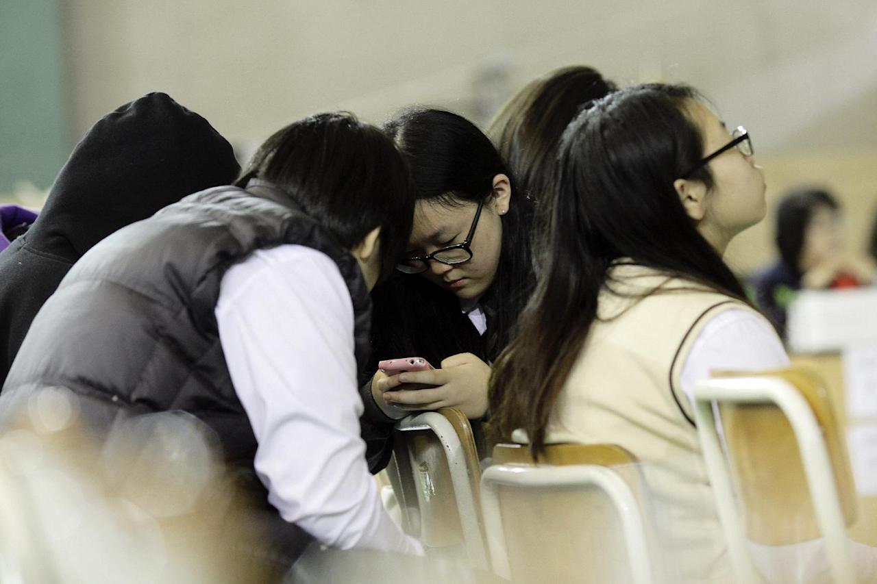 Students check a mobile phone for the latest news on the ferry that sank Wednesday, which was carrying 475 people aboard, including 325 students, at an auditorium in Danwon High School in Ansan, South Korea, Thursday, April 17, 2014. Strong currents, rain and bad visibility hampered an increasingly anxious search Thursday for 287 passengers, many thought to be high school students, still missing more than a day after their ferry flipped onto its side and sank in cold waters off the southern coast of South Korea. (AP Photo/Woohae Cho)