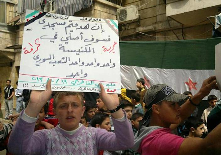 """This citizen journalism image provided by Aleppo Media Center AMC which has been authenticated based on its contents and other AP reporting, shows an anti-Syrian regime protester holds up and Arabic placard that reads: """"if you destroy my mosque I'll pray at the church, one one one the Syrian people is one, freedom, dignity,"""" during a demonstration, in Aleppo, Syria, Friday April 19, 2013. Gunmen killed a government official in a Damascus restaurant, Syrian state media and activists reported Friday as regime troops and rebels fought fierce battles near the Lebanese border.(AP Photo/Aleppo Media Center, AMC)"""