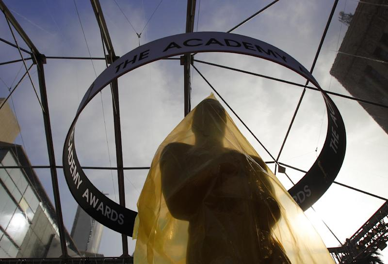 An Oscar statue under a sheet of protective plastic stands on the red carpet outside the Kodak Theatre as preparations continue for the 84th Academy Awards in Los Angeles on Saturday,  Feb. 25, 2012. The Oscars will be held on Sunday. (AP Photo/Amy Sancetta)