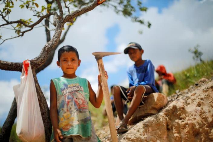 Indigenous children pose for a picture in a gold mine at the Santa Creuza community in the Raposa Serra do Sol reservation