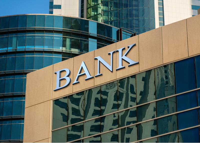 "A high-rise building with a large sign on the roof that reads ""BANK."""