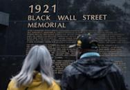 People look at the Black Wall Street Memorial on the 100-year anniversary of the Greenwood race massacre in Tulsa, Oklahoma