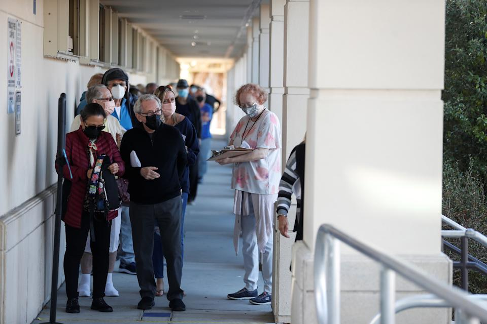 A Florida Department of Health employee helps a senior who is getting the COVID-19 vaccine as people of 65 and over wait in line at the DOH Sarasota COVID-19 Vaccination Clinic in Sarasota, Florida, U.S. January 4, 2021. REUTERS/Octavio Jones