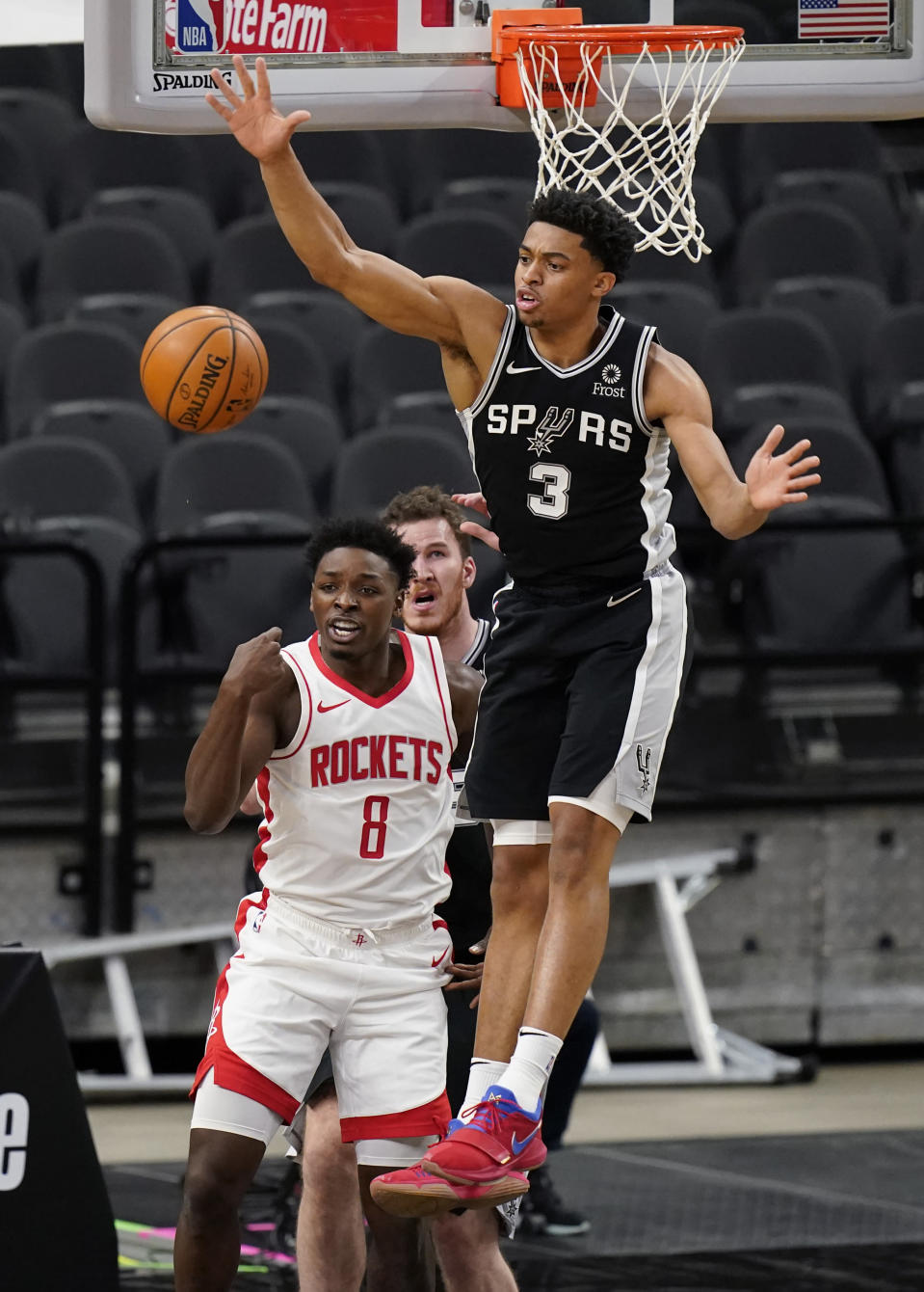 San Antonio Spurs forward Keldon Johnson (3) blocks a shot by Houston Rockets forward Jae'Sean Tate (8) during the first half of an NBA basketball game in San Antonio, Thursday, Jan. 14, 2021. (AP Photo/Eric Gay)