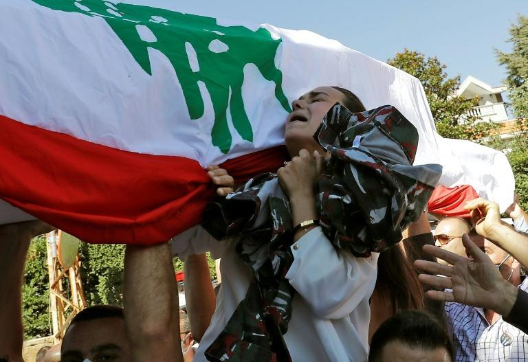 Karlen weaps during the funeral procession of her husband Charbel Karam, brother Najib Hitti, and cousin Charbel Hitti in the firefighters' hometown of Qartaba, north of the Lebanese capital Beirut