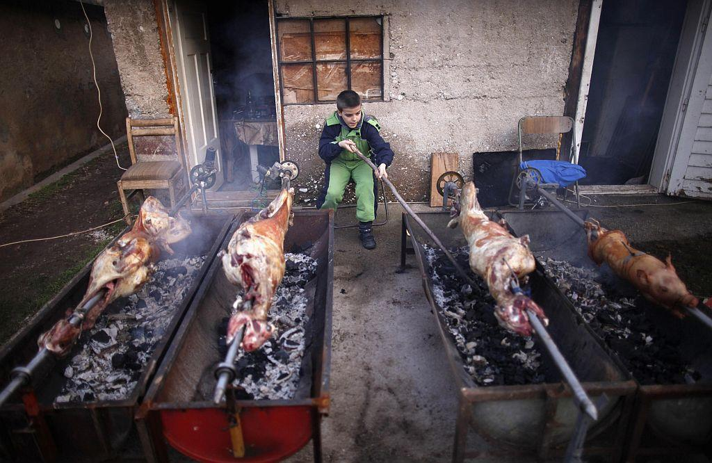 BOSNIA AND HERZEGOVINA: Bosnian Serb boy roasts lamb and pig for a traditional Orthodox Christmas meal, in front of his home in the village of Vojkovici, near the capital of Sarajevo January 6, 2013. Orthodox Christians mark Christmas according to the Julian calendar on January 7.