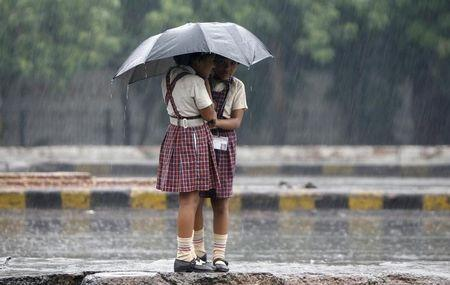 Schoolgirls stand on a road divider as they huddle under an umbrella during monsoon rain in New Delhi
