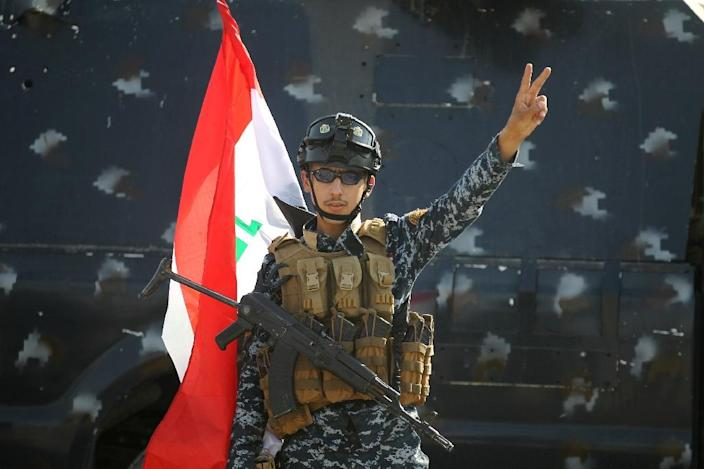 """An Iraqi federal police member flashes the sign for victory as he celebrates in the Old City of Mosul on July 9, 2017 after the government's announcement of the """"liberation"""" of the embattled city (AFP Photo/AHMAD AL-RUBAYE)"""