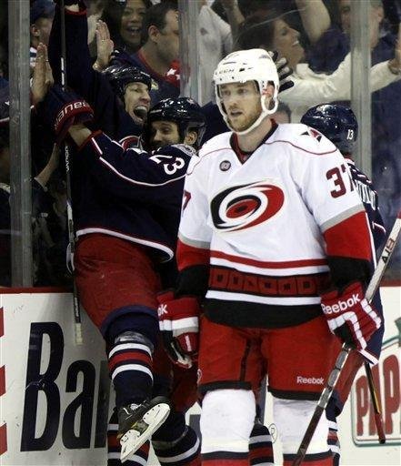 Carolina Hurricanes' Tim Brent (37) skates by while Columbus Blue Jackets' RJ Umberger, left, celebrates with Brett Lebda (23) after he scored his third goal during the third period of an NHL hockey game on Friday, March 23, 2012, in Columbus, Ohio. The Blue Jackets won 5-1. (AP Photo/Terry Gilliam)
