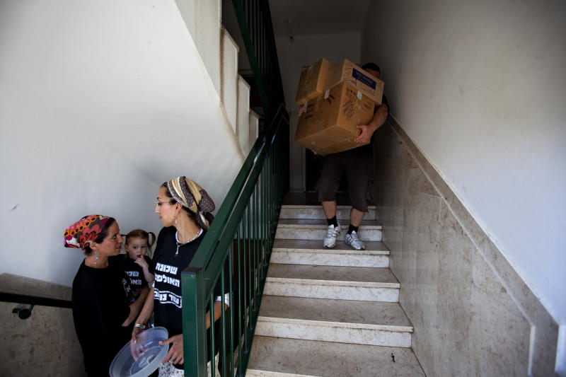 Jewish settlers watch as movers employed by the Israeli Defense Ministry carry out belongings from settler's apartment in the Ulpana neighborhood in the West bank Jewish settlement of Beit El, near Ramallah, Tuesday, June. 26, 2012. Israel has started on Tuesday to evacuate about 30 families fromthe Ulpanaunauthorized West Bank outpost, following a court order to dismantle the enclave, to be followed by 30 more later this week.Ulpana residents have promised to leave quietly unlike more violent evacuations in the past. (AP Photo/Oded Balilty)
