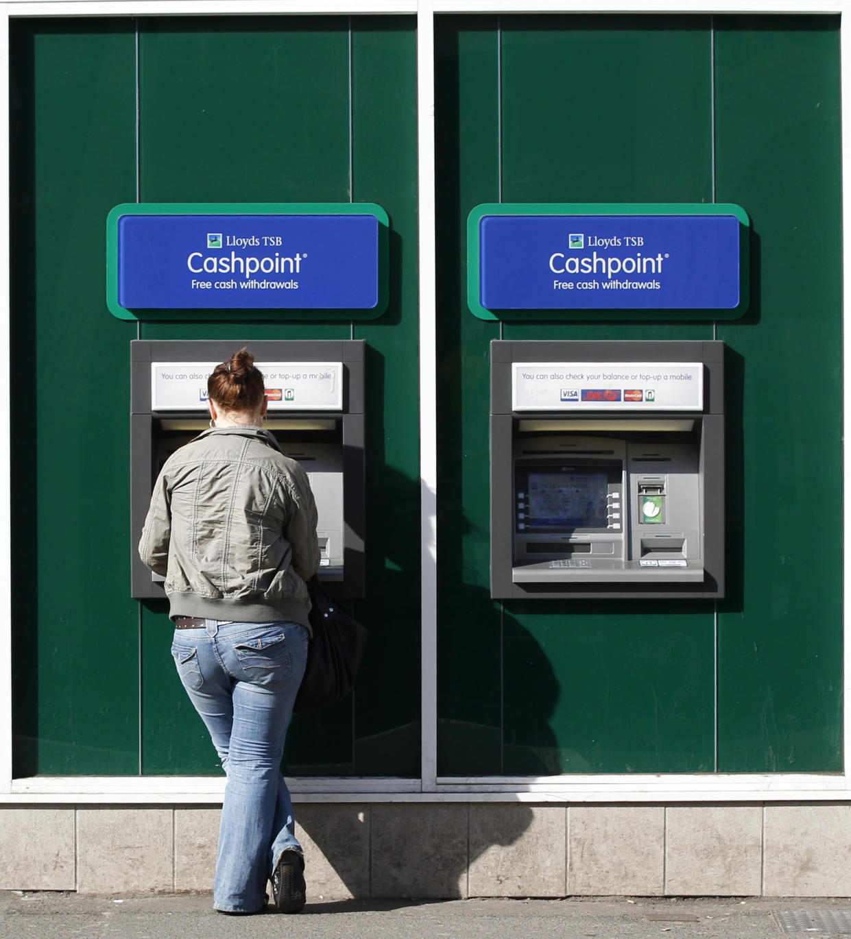 A woman uses a Lloyds TSB Cashpoint machine in Loughborough, central England April 27, 2010.  Lloyds Banking Group returned to profit in the first three months of this year, earlier than expected, as losses on both retail and commercial bad debts for Britain's largest bank continue to fall.  REUTERS/Darren Staples   (BRITAIN - Tags: BUSINESS)