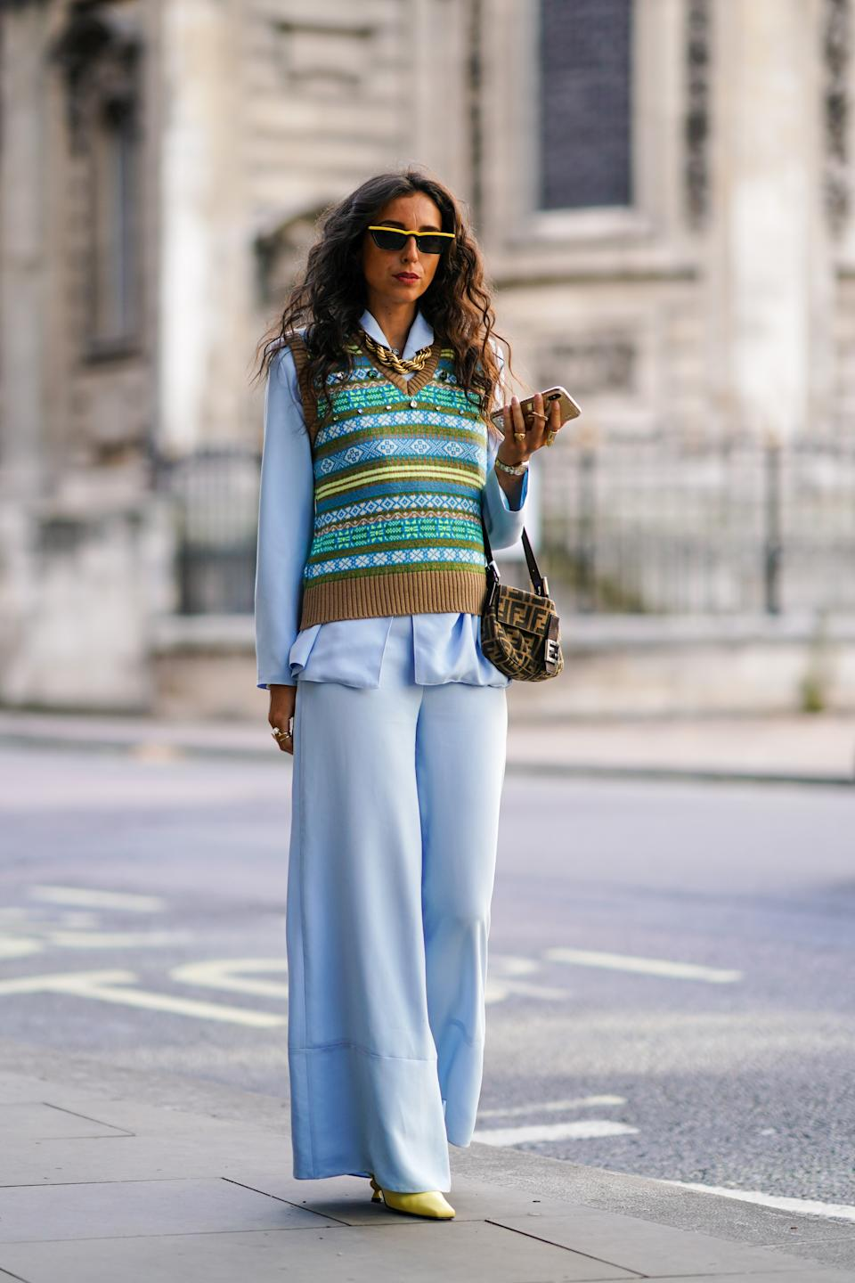 Gabriella Berdugo is seen wearing a pale blue two-set layered with a statement knit and Fendi bag. [Photo: Getty Images]