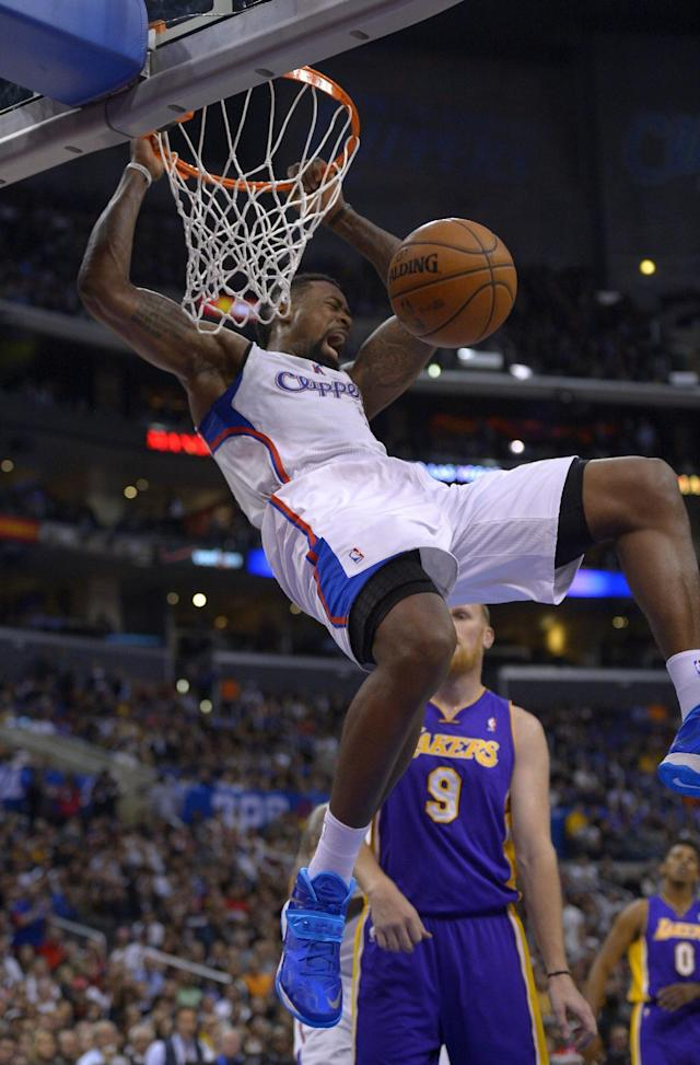 Los Angeles Clippers forward Jared Dudley, top, dunks as Los Angeles Lakers center Chris Kaman looks on during the first half of an NBA basketball game, Friday, Jan. 10, 2014, in Los Angeles. (AP Photo/Mark J. Terrill)