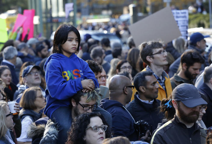 <p>Nat Vandyke, 7, rides on his father's shoulders as they join a march of demonstrators protesting President-elect Donald Trump, Sunday, Nov. 13, 2016 in New York. Organizers said the protest was about speaking out against Trump's support of deportation and other measures. (AP Photo/Mark Lennihan) </p>
