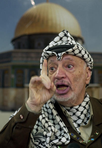 FILE - In this Dec. 24, 2002 file photo, Palestinian leader Yasser Arafat talks to the media during a press conference at his headquarters, in the West Bank town of Ramallah. The widow of Yasser Arafat on Tuesday July 31, 2012 formally asked for a French investigation into his death, bringing a complaint of assassination weeks after raising new suspicions that the former Palestinian leader was poisoned before his 2004 death in a French military hospital. Earlier this month, Palestinian authorities gave final approval for Arafat's body to be exhumed. (AP Photo/Muhammed Muheisen, File)