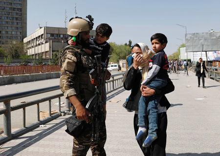 Rescued children are carried from the building of Ministry of Communication and Information Technology in Kabul