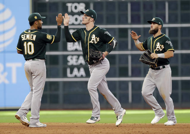 Oakland Athletics' Marcus Semien (10), Mark Canha, center, and Nick Martini celebrate after a baseball game against the Houston Astros Thursday, July 12, 2018, in Houston. The Athletics won 6-4. (AP Photo/David J. Phillip)