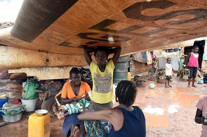 A family rests under the wing of a derelict plane on May 3, 2014 at a refugee camp at Bangui's Mpoko airport (AFP Photo/Issouf Sanogo)