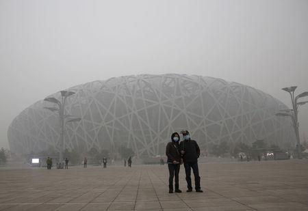 """Visitors wearing protective masks take a selfie in front of the National Stadium, also known as the """"Bird's Nest"""", on an extremely polluted day as hazardous, choking smog continues to blanket Beijing, China December 1, 2015. REUTERS/Kim Kyung-Hoon"""