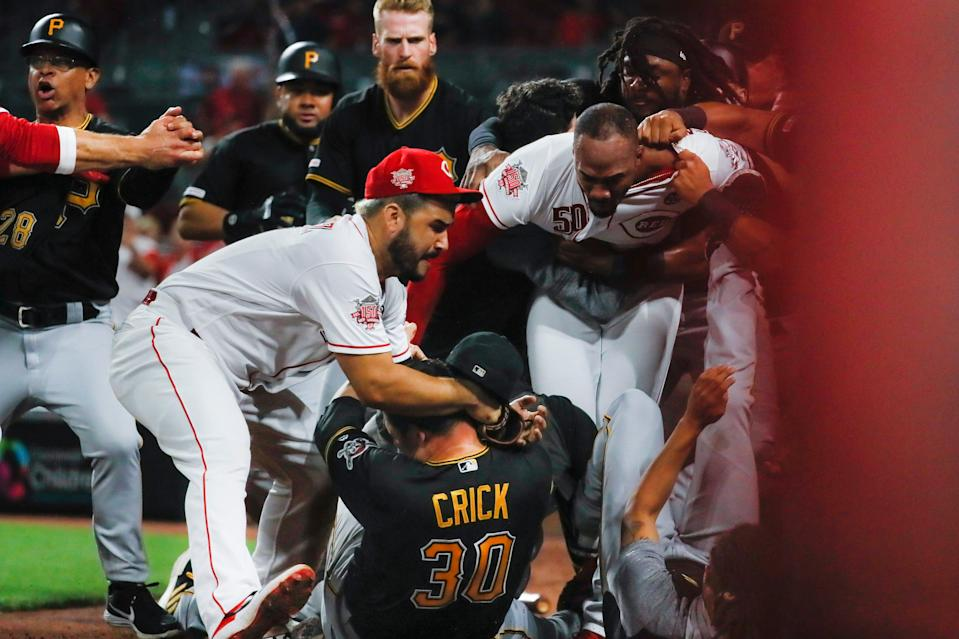 Pirates reliever Kyle Crick (30) falls between Eugenio Suarez, left, and Amir Garrett of the Reds during a brawl in 2019, one of several incidents involving Garrett in recent years.