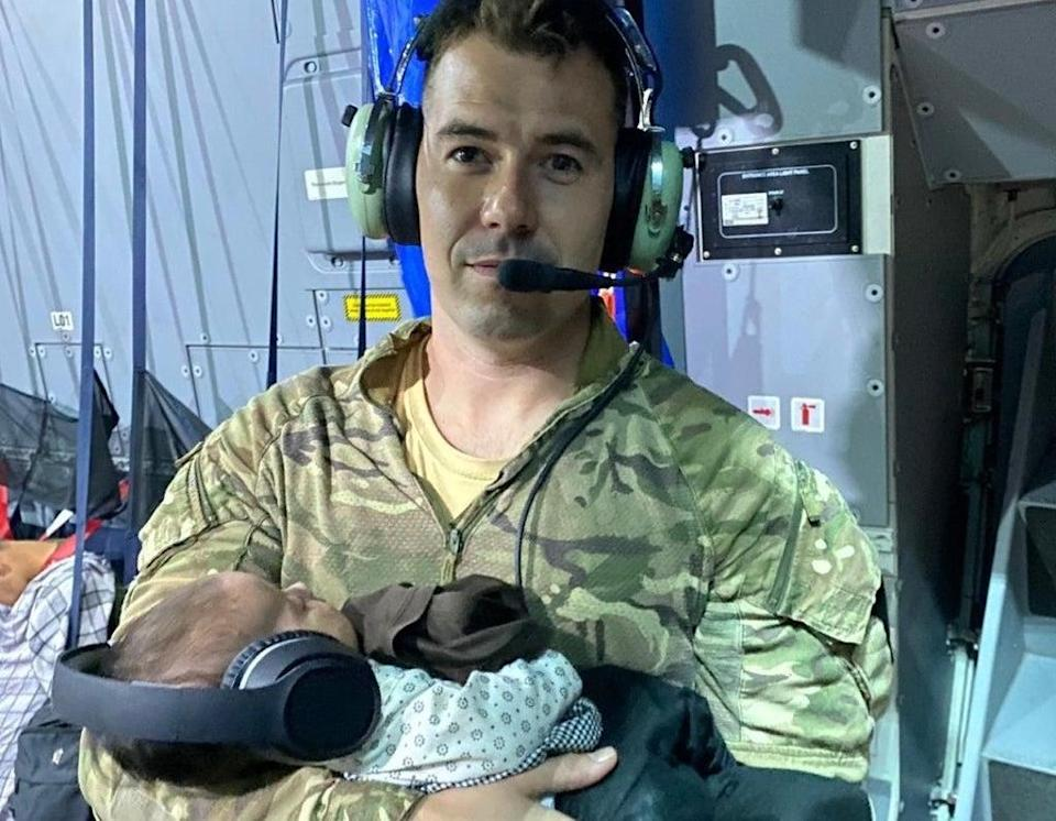 Sgt Andy Livingstone holding a baby Afghan girl while she and her mother slept   (Ministry of Defence)