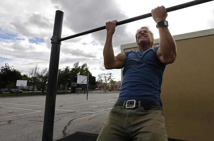 Mike Lynn grimaces as he does a pull-up on playground exercise equipment.