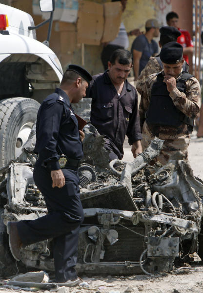 Security forces inspect the scene of a car bomb attack in Basra, 340 miles (550 kilometers) southeast of Baghdad, Sunday, Sept. 9, 2012. In violence, which struck at least 10 cities across the nation, insurgents killed at least 39 people in a wave of attacks against Iraqi security forces on Sunday, gunning down soldiers at an army post and bombing police recruits waiting in line to apply for jobs, officials said. (AP Photo/Nabil al-Jurani)
