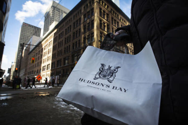 A woman holds a Hudson's Bay shopping bag in front of the Hudson's Bay Company flagship department store in Toronto.