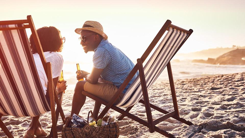 Shot of a happy young couple relaxing on chairs and having drinks at sunset on the beach.