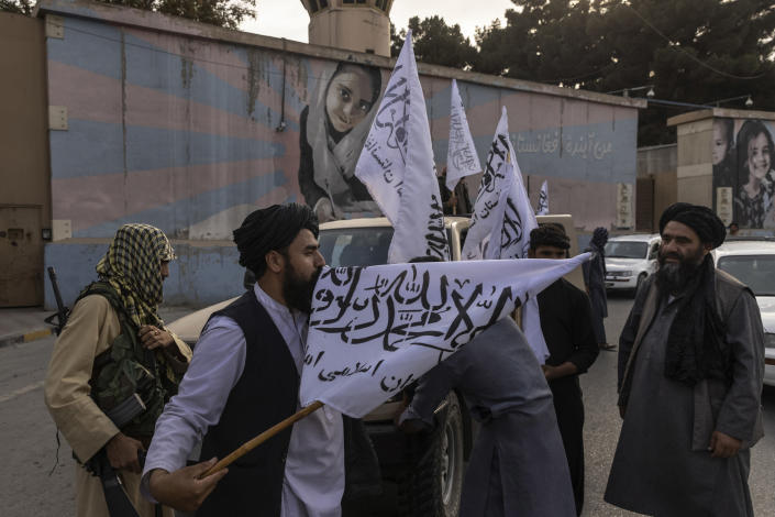 Taliban fighters wave their flag outside the U.S. Embassy in Kabul, Afghanistan, on Sunday, Aug. 22, 2021. (Victor J. Blue/The New York Times)