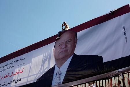 FILE PHOTO: A photographer sits on a billboard poster of a Yemen's President Abd-Rabbu Mansour Hadi during a ceremony commemorating the anniversary of the 2011 uprising that toppled Yemen's former president Ali Abdullah Saleh in Taiz, Yemen February 11, 2018. REUTERS/Anees Mahyoub/File Photo