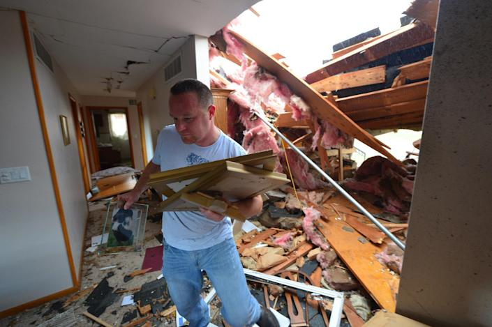 Josh Ramsey recovers items from a house of a family friend after a tornado left a path of devastation through the north end of Pekin, Ill., hitting right about noon Sunday, Nov. 17, 2013. Intense thunderstorms and tornadoes swept across the Midwest on Sunday, causing extensive damage in several central Illinois communities while sending people to their basements for shelter. (AP Photo/Journal Star, Fred Zwicky) MANDATORY CREDIT