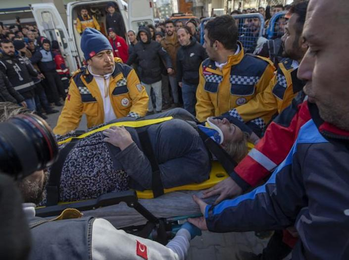 A woman, trapped for 14 hours, is rescued from the rubble in Elazig after a 6.8-magnitude earthquake rocked eastern Turkey: Anadolu Agency via Getty