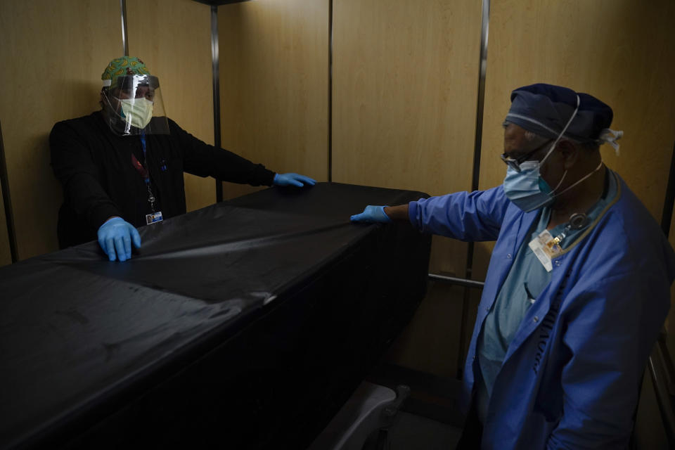 FILE - In this Jan. 9, 2021, file photo, transporters Miguel Lopez, right, Noe Meza move a body of a COVID-19 patient to a morgue at Providence Holy Cross Medical Center in the Mission Hills section of Los Angeles. Coronavirus hospitalizations are falling across the United States, but deaths have remained stubbornly high. (AP Photo/Jae C. Hong, File)