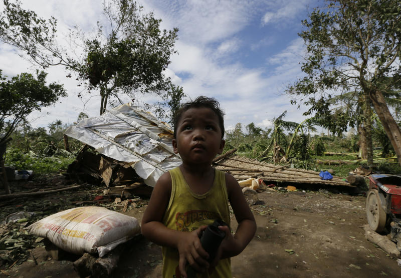 A child stands near his family's damaged house Wednesday Dec. 5, 2012, a day after powerful Typhoon Bopha hit Montevista township Compostela Valley in southern Philippines. Typhoon Bopha, one of the strongest typhoons to hit the Philippines this year, barreled across the country's south on Tuesday, killing scores of people while triggering landslides, flooding and cutting off power in two entire provinces. (AP Photo/Bullit Marquez)