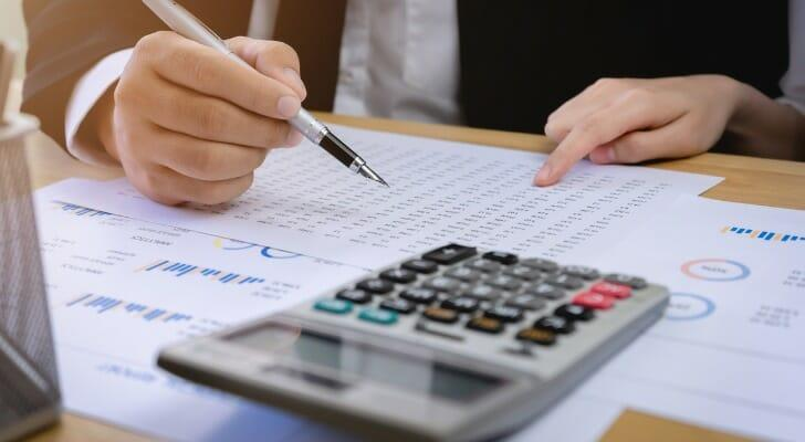 Businessman using a calculator to make investment decisions.