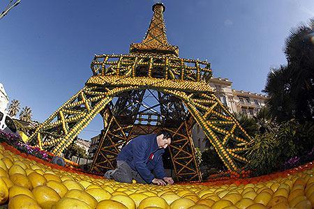 """FRANCE: A worker puts the final touch at a sculpture featuring the Eiffel tower made from lemons and oranges during the lemon festival in Menton, southern France, February 16, 2012. Some 145 metric tons of lemons and oranges are used to make displays during the 79th festival, which is themed """"The regions of France"""", and runs from February 17 through March 7."""